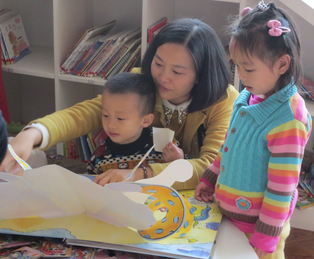 Mom and kids exploring a pop-up book after storytime at Baby Cube.
